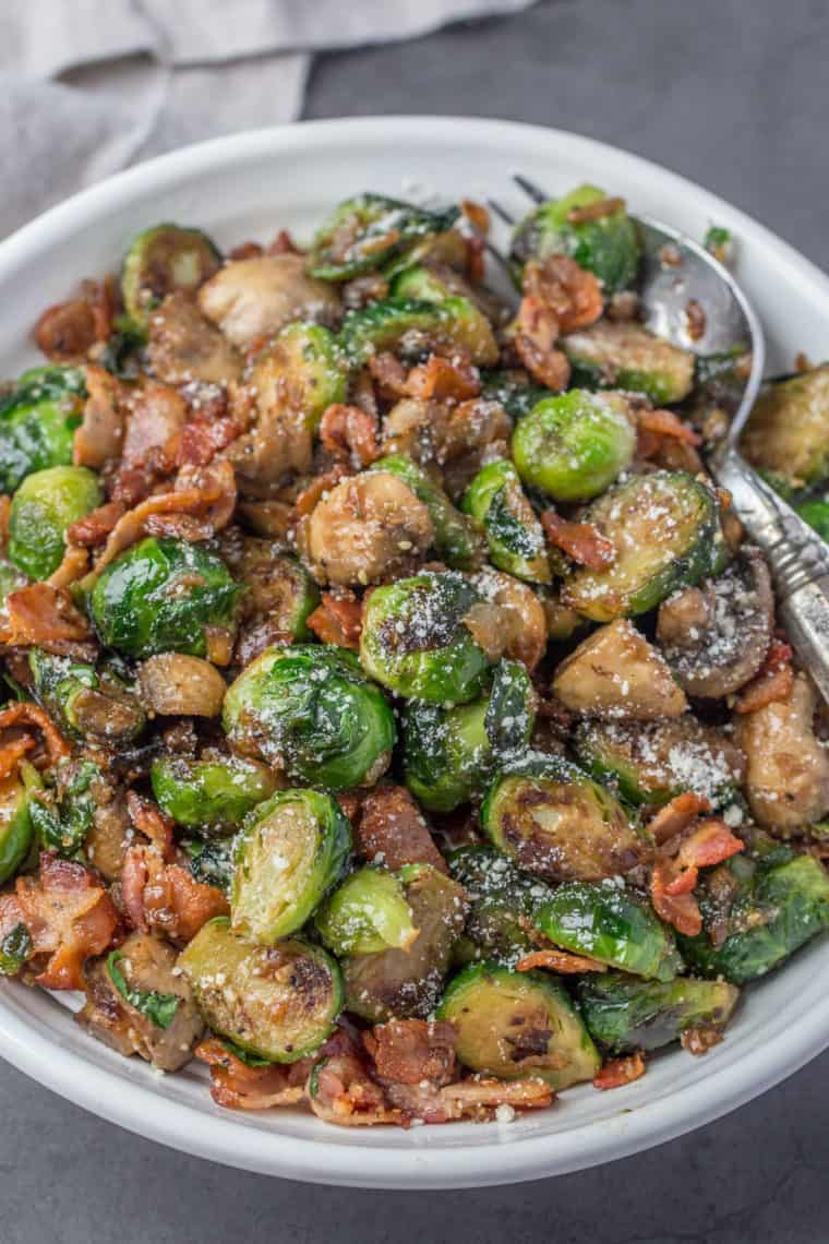 Brussel sprouts in a white bowl with a spoon loaded with mushrooms and bacon.