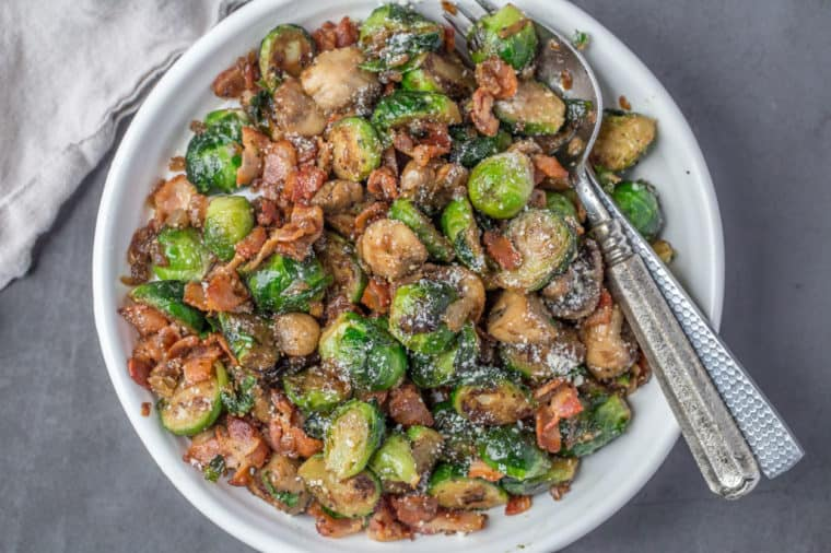 Crispy brussel sprouts with mushrooms and bacon in a white bowl topped with parmesan cheese.