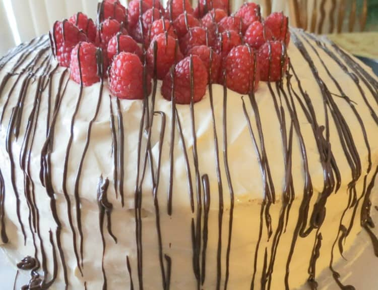 Layered sponge cake topped with fresh raspberries and chocolate drizzle.