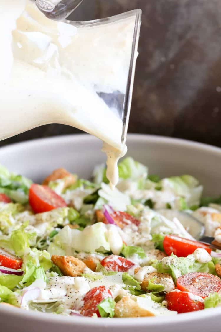 Caesar salad dressing pouring into salad bowl that is loaded with lettuce, tomatoes, croutons, and onions.