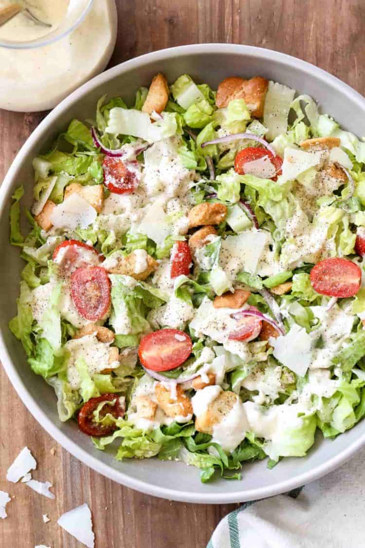 A bowl of salad with the Caesar salad dressing drizzled on top of the salad.