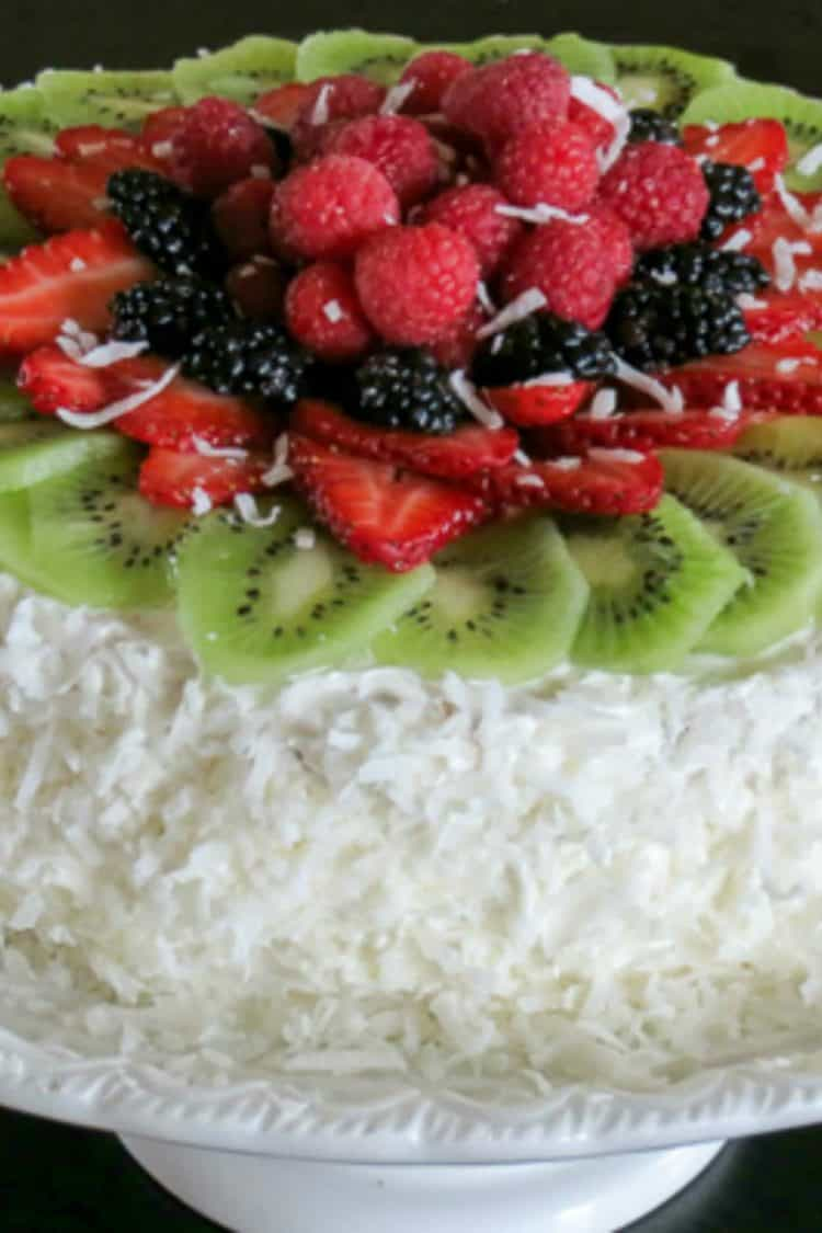 Layered sponge cake on a white cake stand topped with fresh fruit and coconut shavings.