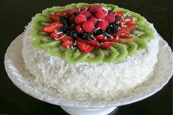 Layered sponge cake with fruits on a cake platter topped with fruits and coconut shavings.