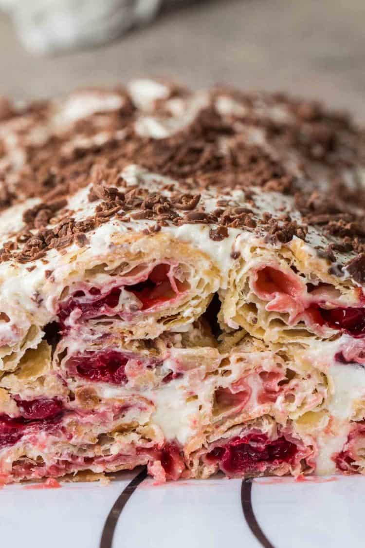 Puff pastry cake with a cherry filling and smothered in a sweet cream and topped with chocolate shavings.