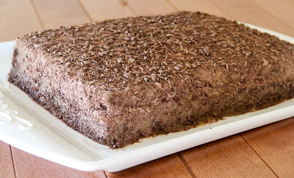 Poppy seed cake on a cake platter topped with chocolate shavings.