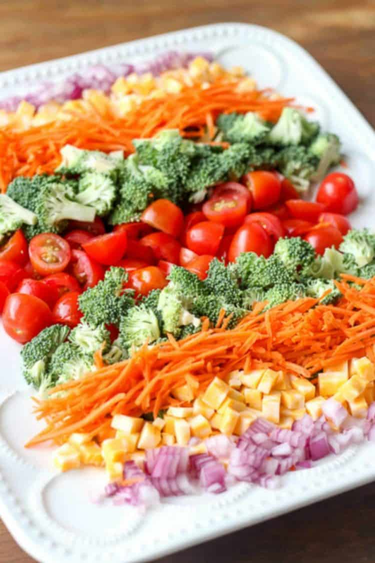 Simple recipe for broccoli cheese tomato salad with carrots, cheese, and onions.
