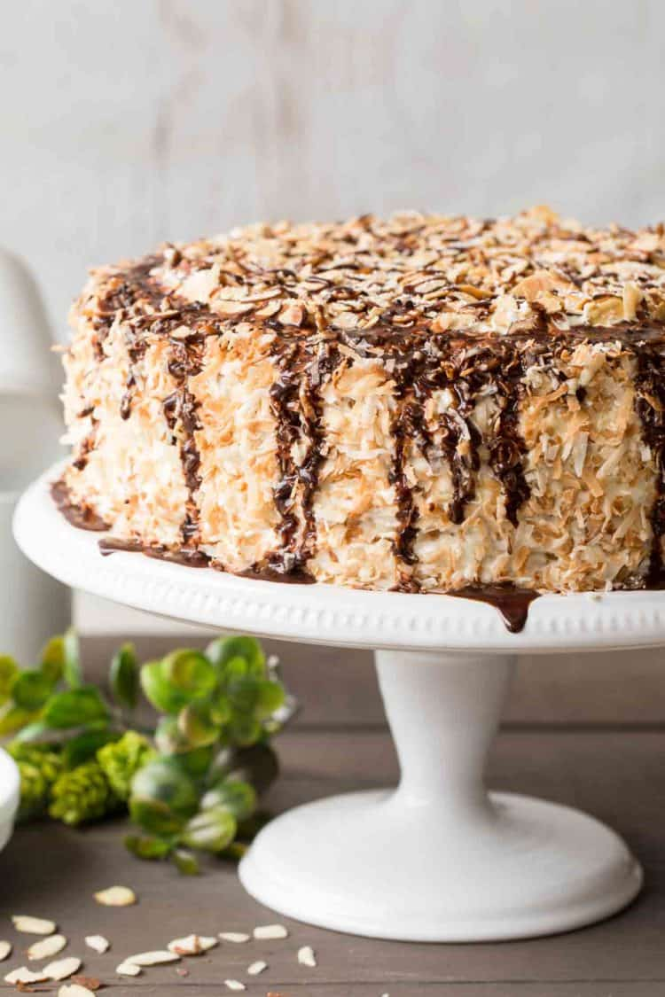 Layered coconut cake recipe on a cake stand with chocolate drizzle and toasted coconuts.