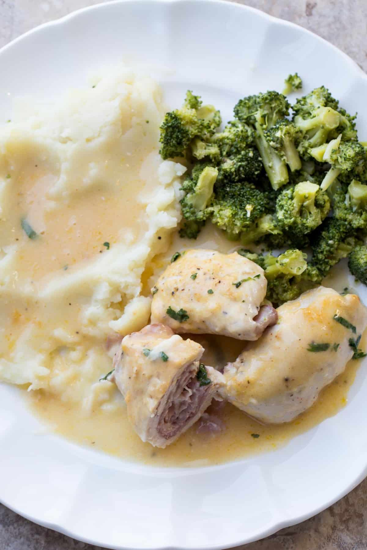 Chicken cordon bleu with mashed potatoes and a side of broccoli.