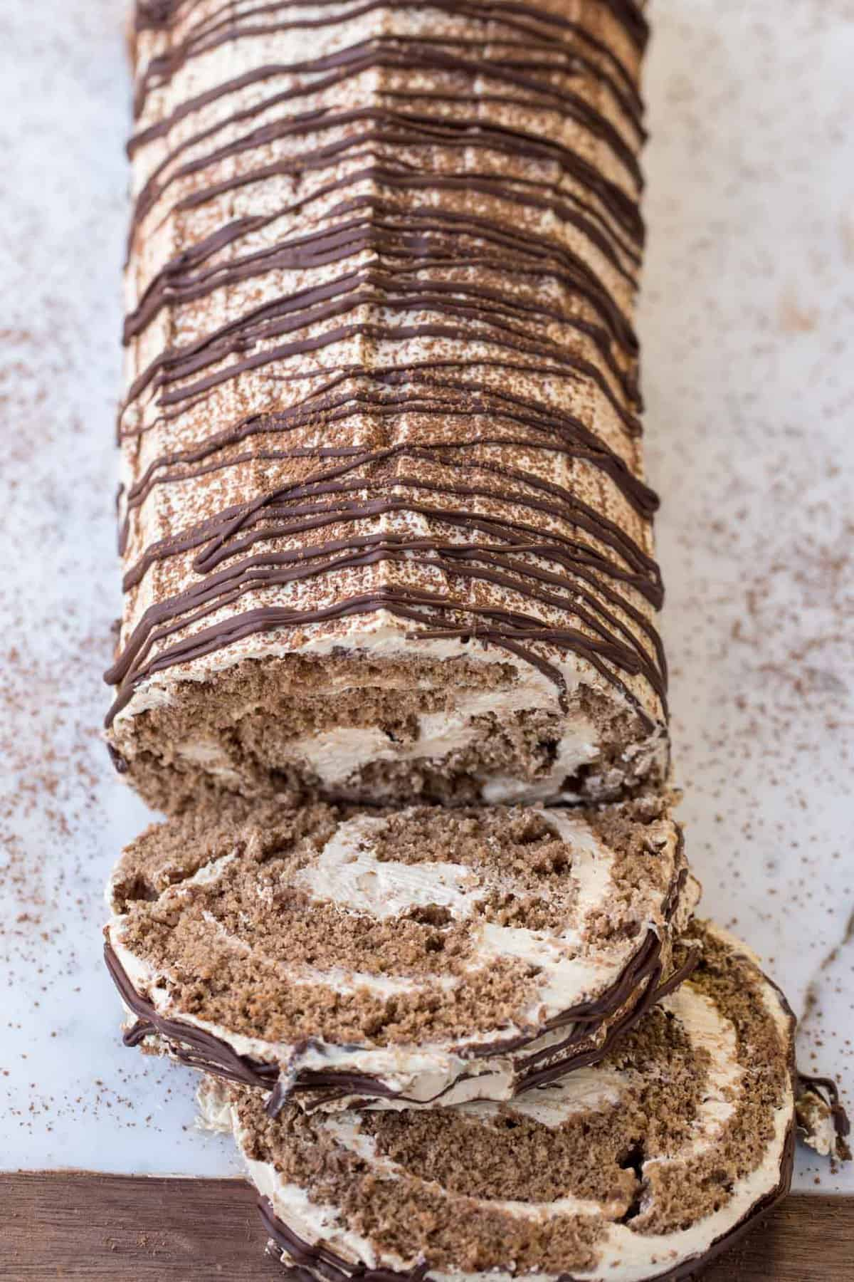 Coffee Roulade with chocolate sponge cake and a sweet coffee cream on a marble serving platter.