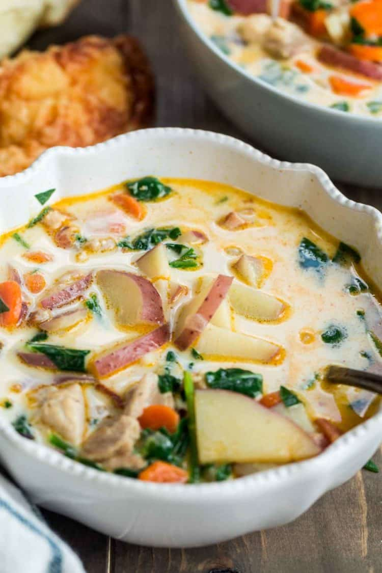 Potato soup with chicken, carrots, and spinach in a bowl next to a bagel and another bowl of soup.