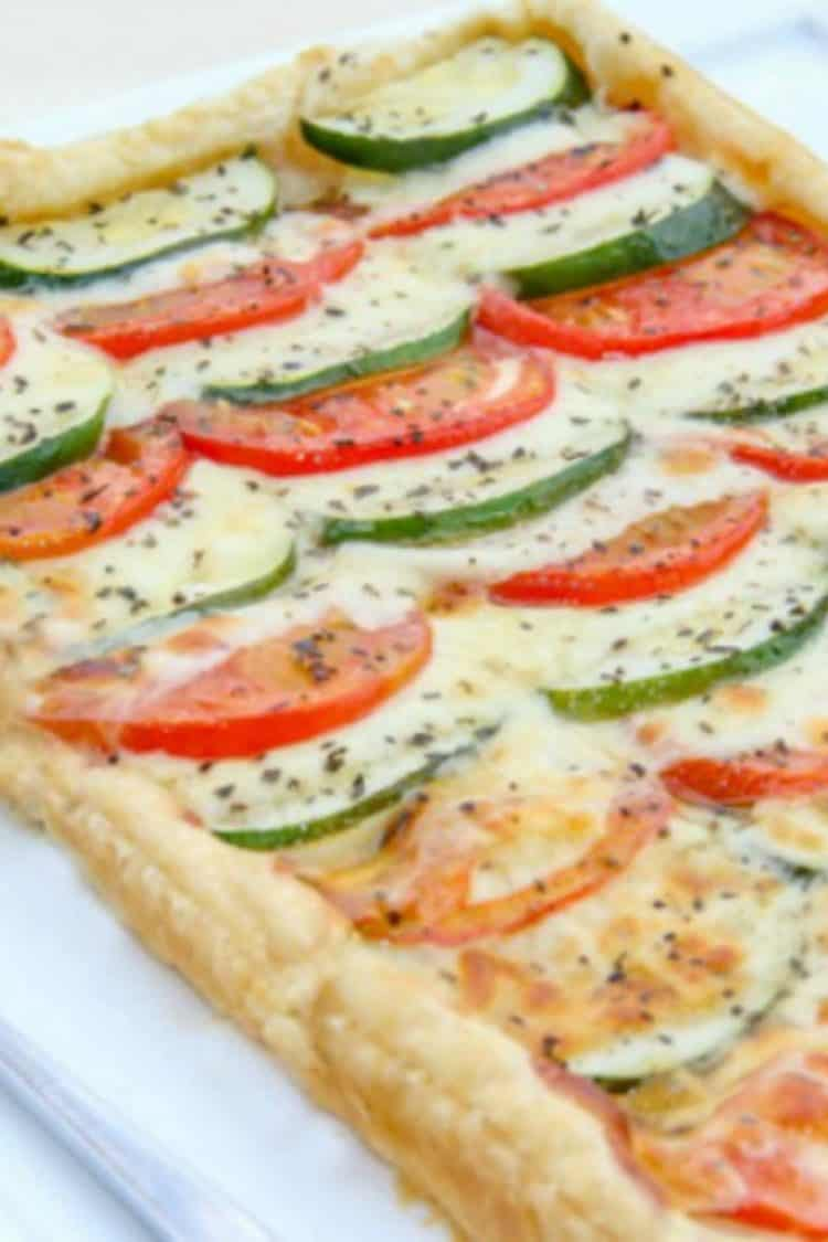 Tomato Zucchini and Cheese Tart on a platter topped with fresh grated pepper.