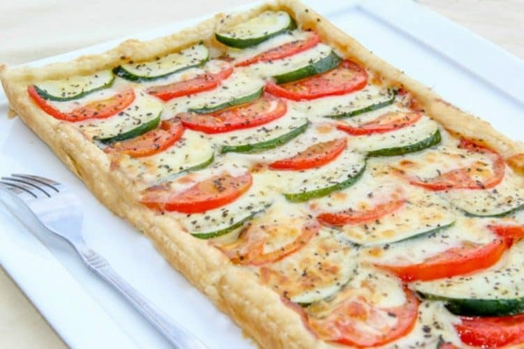 Tomato Zucchini and Cheese Tart on a platter topped with pepper and next to a fork.