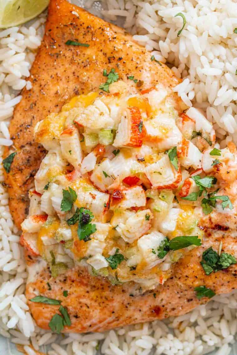 Crab stuffed salmon over a bed of rice topped with fresh chopped greens.