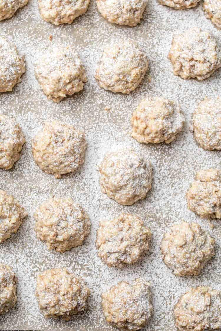 Walnut cookies laid out on a parchment paper dusted with powdered sugar.