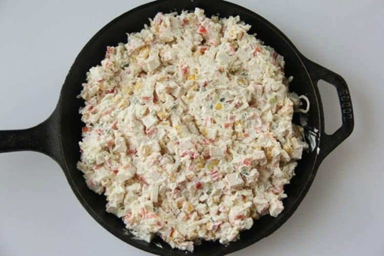 Crab dip in a cast iron skillet mixed and ready to be baked in the oven.