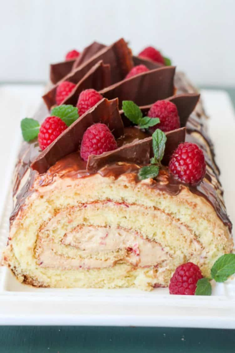 Cake roulade on a cake platter topped with chocolate and fresh raspberries.
