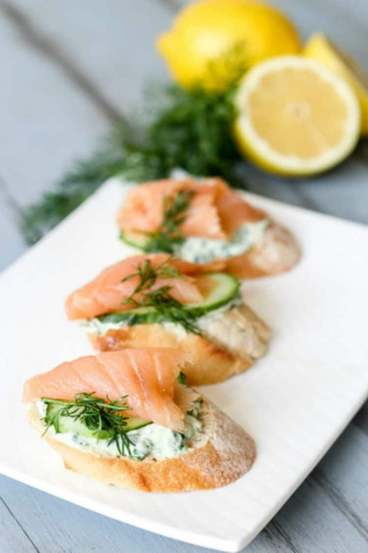 Salmon yogurt canapes on a plate next to fresh dill and lemons.