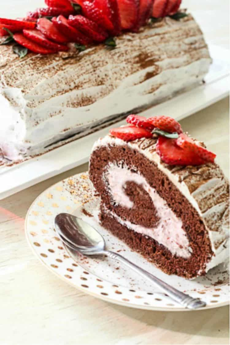 A chocolate roulade with fresh strawberries next to a slice of chocolate roulade on a plate.