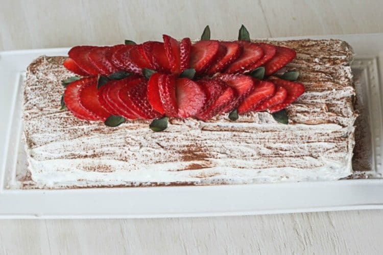 Chocolate roulade with strawberries on a tray topped with cocoa powder and fresh strawberries.