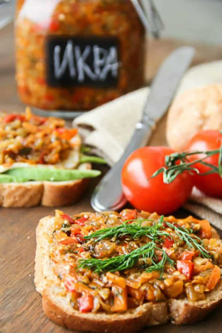 Chunky eggplant vegetable spread on bread next to a knife and tomatoes.