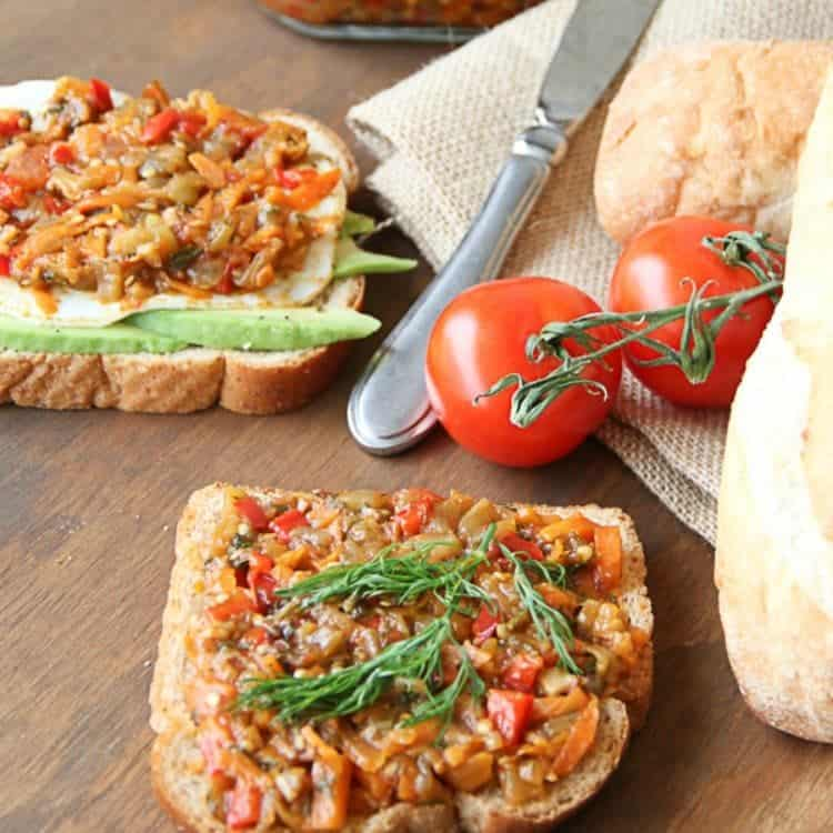 Eggplant spread, ikra on toast next to a butter knife, bread and tomatoes.