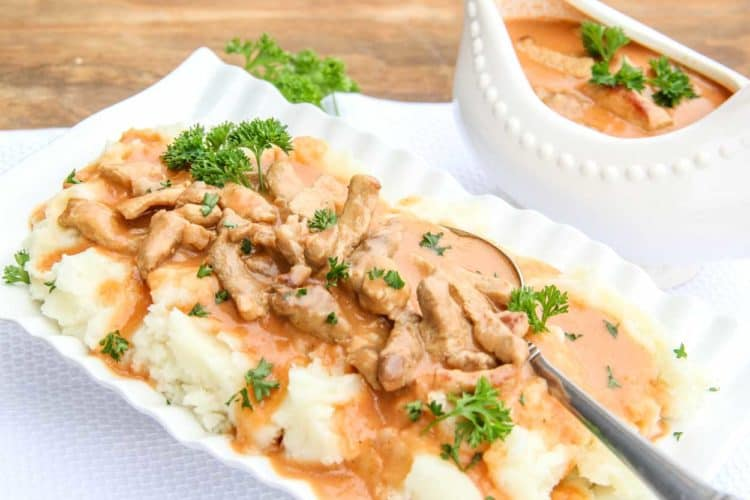An easy gravy recipe in a bowl with mashed potatoes topped with fresh chopped greens.