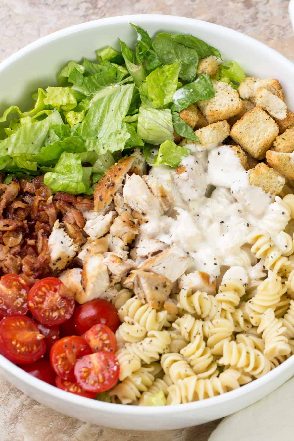 Pasta salad with romaine, bacon, chicken and croutons with a Caesar salad dressing in a white salad bowl.