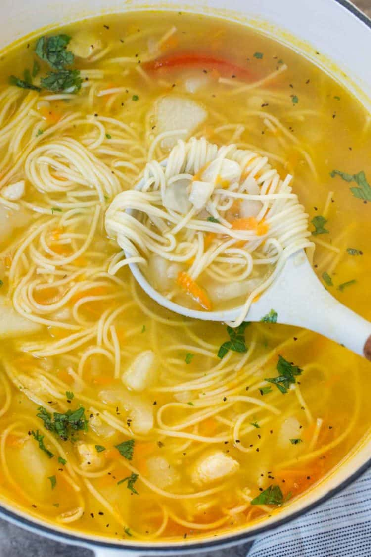 Classic Russian soup in a ladle with potatoes, noodles and fresh chopped greens.