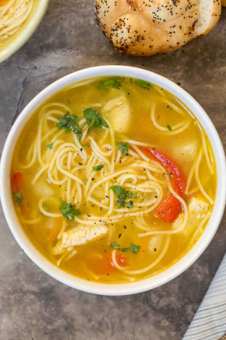 Chicken soup in a bowl with a red pepper and topped with fresh greens and pepper.
