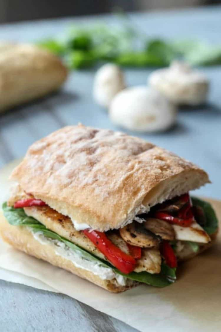 Chicken Sandwich Recipe with chicken breast, peppers, cheese and mushrooms as a sandwich on parchment paper.