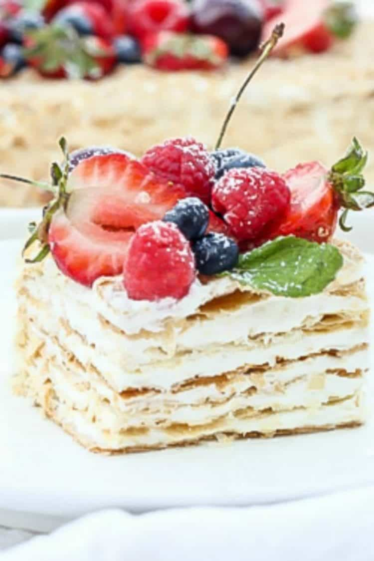 A slice of layered pastry cake on a plate topped with fresh fruits.