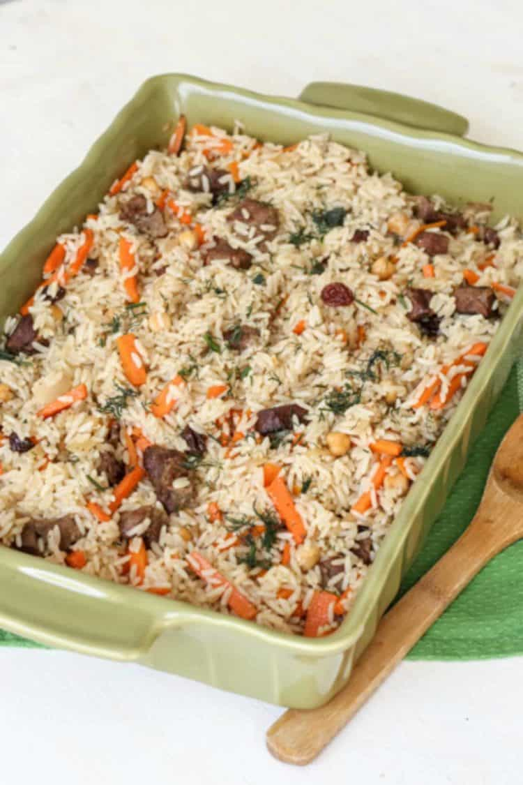 Baked rice pilaf (plov) in a casserole dish with a spoon next to it.