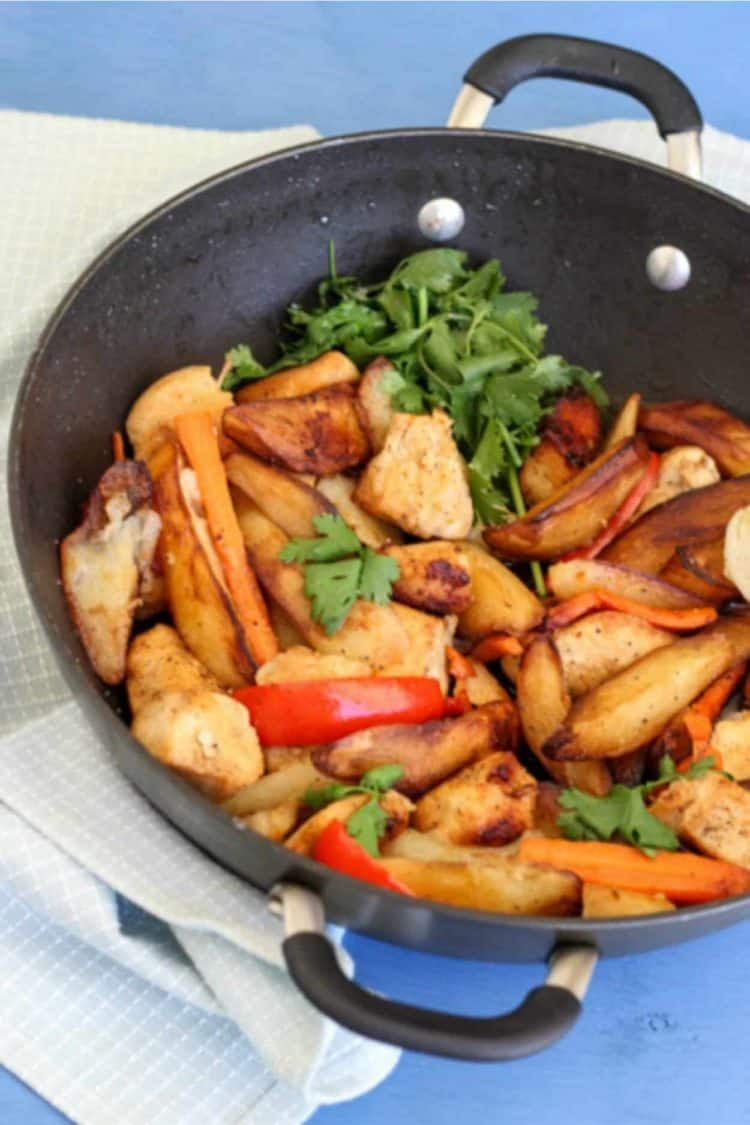 Pan fried potatoes with meat in a skillet with carrots and peppers and fresh greens.
