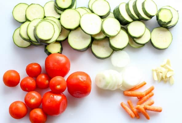 Sliced zucchini and onions on a cutting board next to tomatoes, garlic, and baby carrots.
