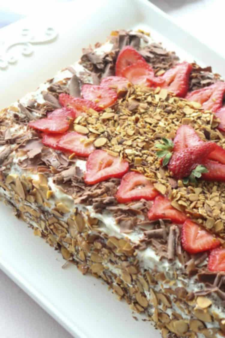 Chocolate cake recipe on a cake platter topped with almonds, chocolate and strawberries.