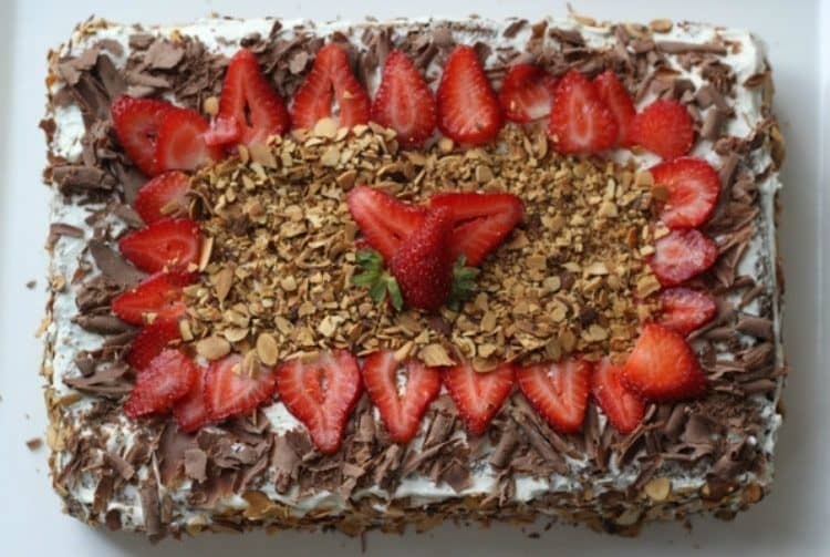 Chocolate cake recipe topped with fresh strawberries, chocolate shavings, and toasted almonds.