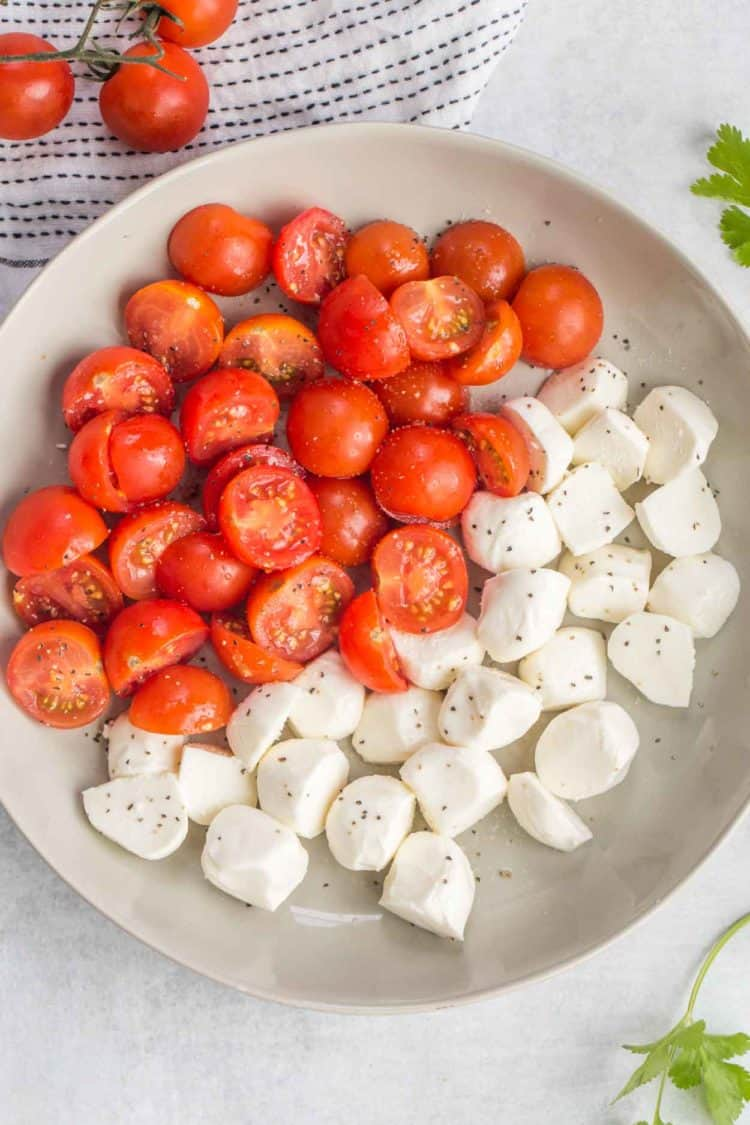 Cut up tomatoes and mozzarella cheese in a bowl topped with ground black pepper.