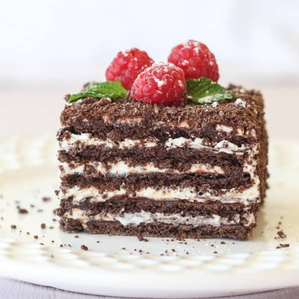 No bake chocolate layer cake on a plate topped with fresh raspberries.