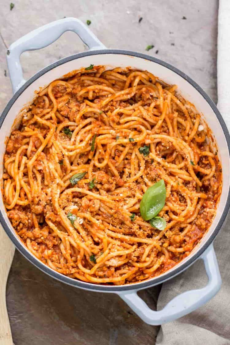 Easy meaty spaghetti recipe in a pot topped with fresh greens, and Parmesan cheese.