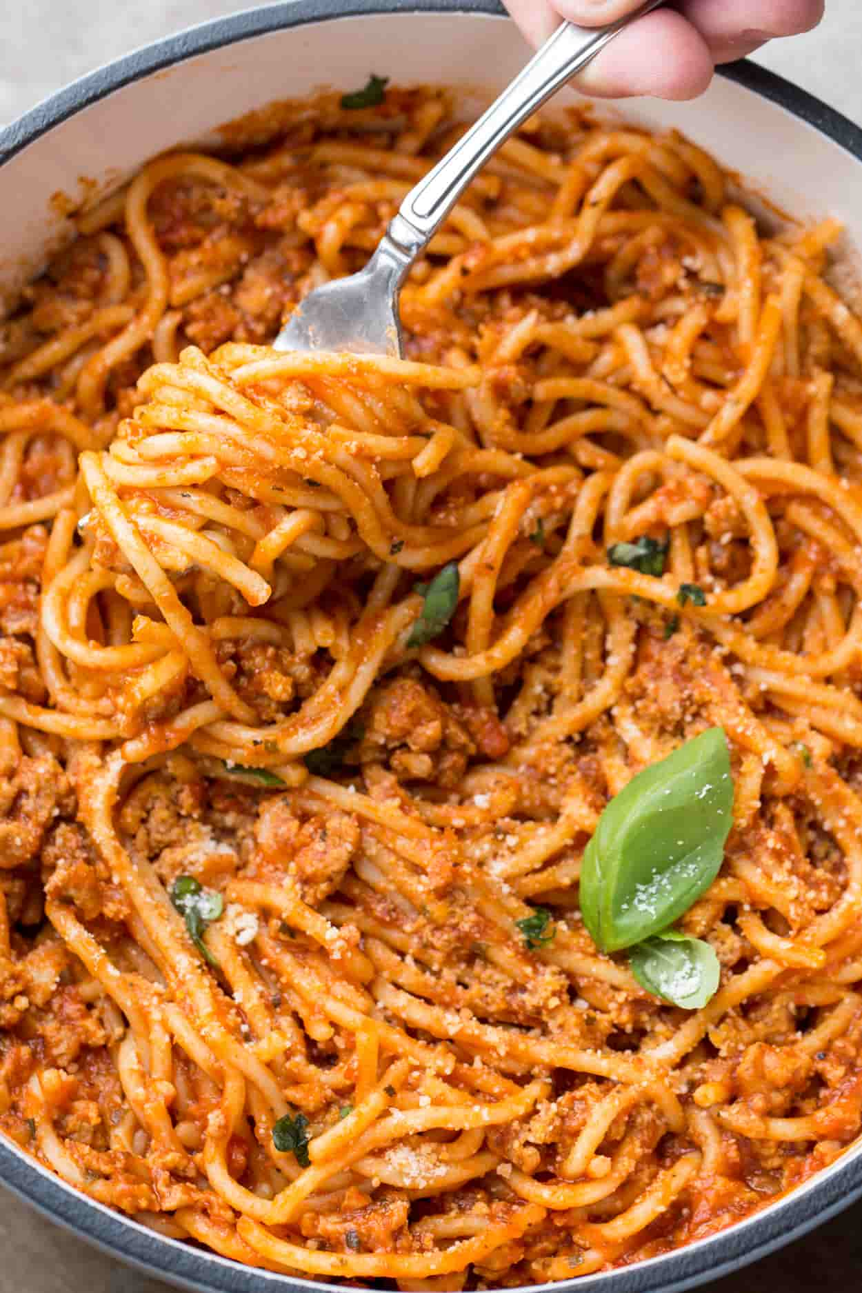 Recipe for how to cook spaghetti. Spaghetti on a fork, topped with Paremsan cheese.
