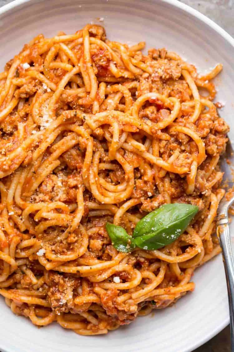 Easy meaty spaghetti in a plate with a fork and topped with Parmesan cheese.