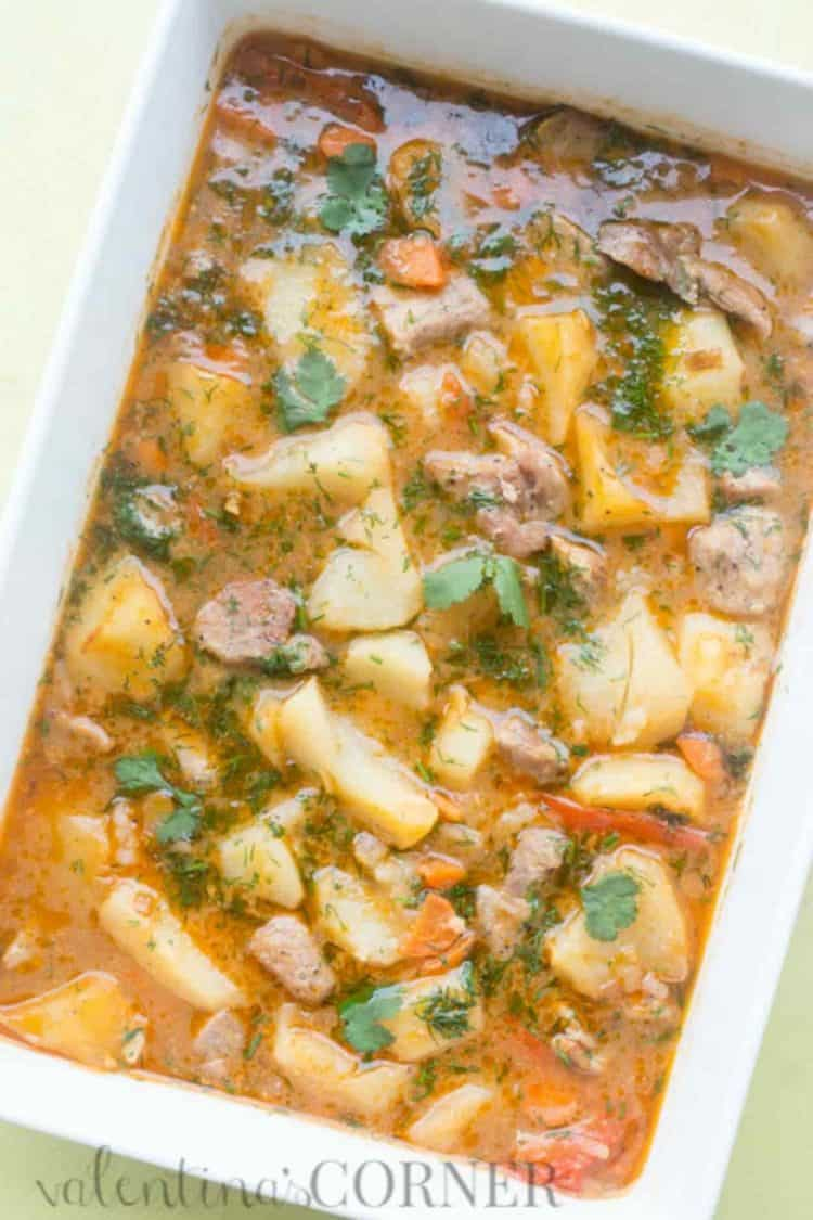 Baked braised potatoes in a casserole dish, potatoes with meat and vegetable cooked in a creamy sauce.