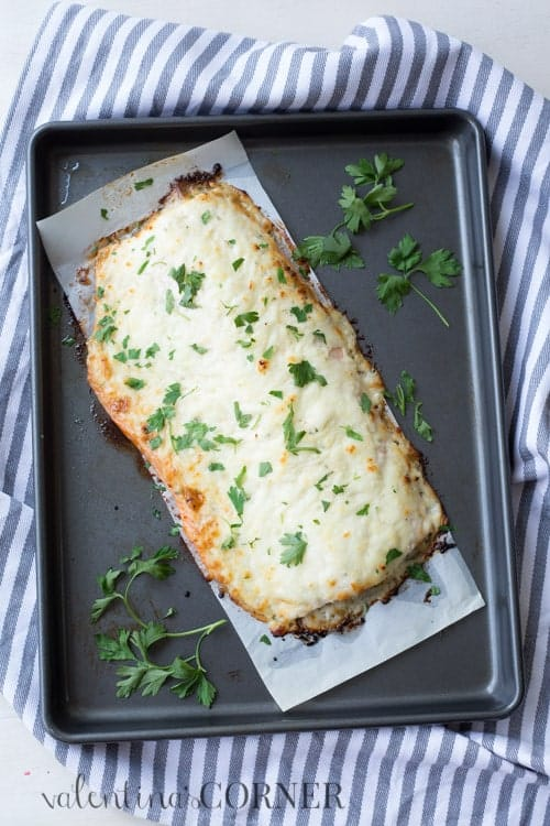 Ranch Baked Salmon topped with fresh herbs on a baking sheet.