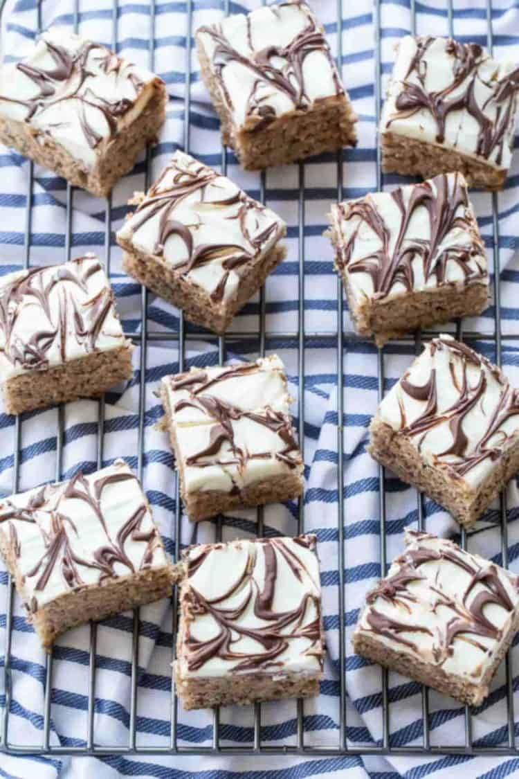 Banana Zucchini Cake Bars on a cooling rack with a cream cheese frosting.