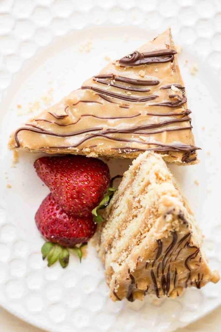 Layered snickers cake recipe on a plate with two pieces and strawberries.