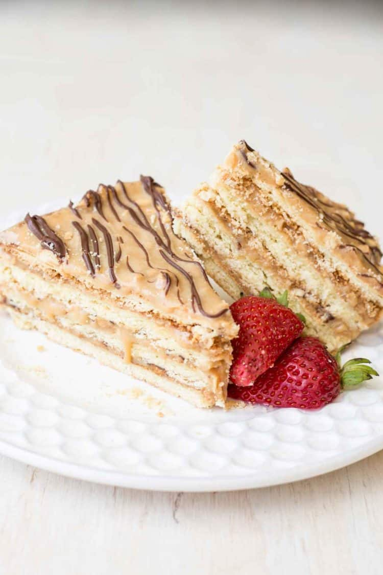 Two pieces of layered snickers cake on a plate next to strawberries.