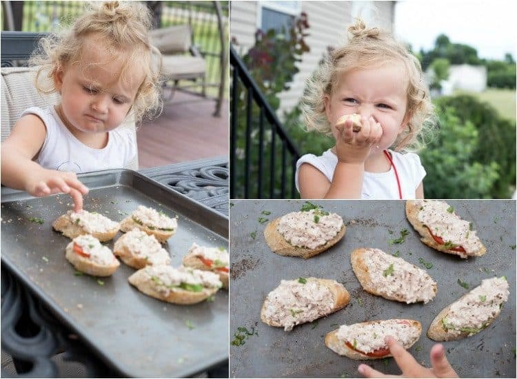 Baby eating tuna and egg canapes with an avocado and tomatoes.