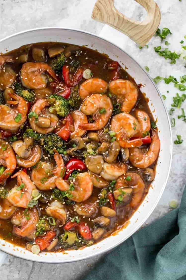 Easy shrimp recipe with vegetables in a skillet topped with fresh greens and sesame seeds.