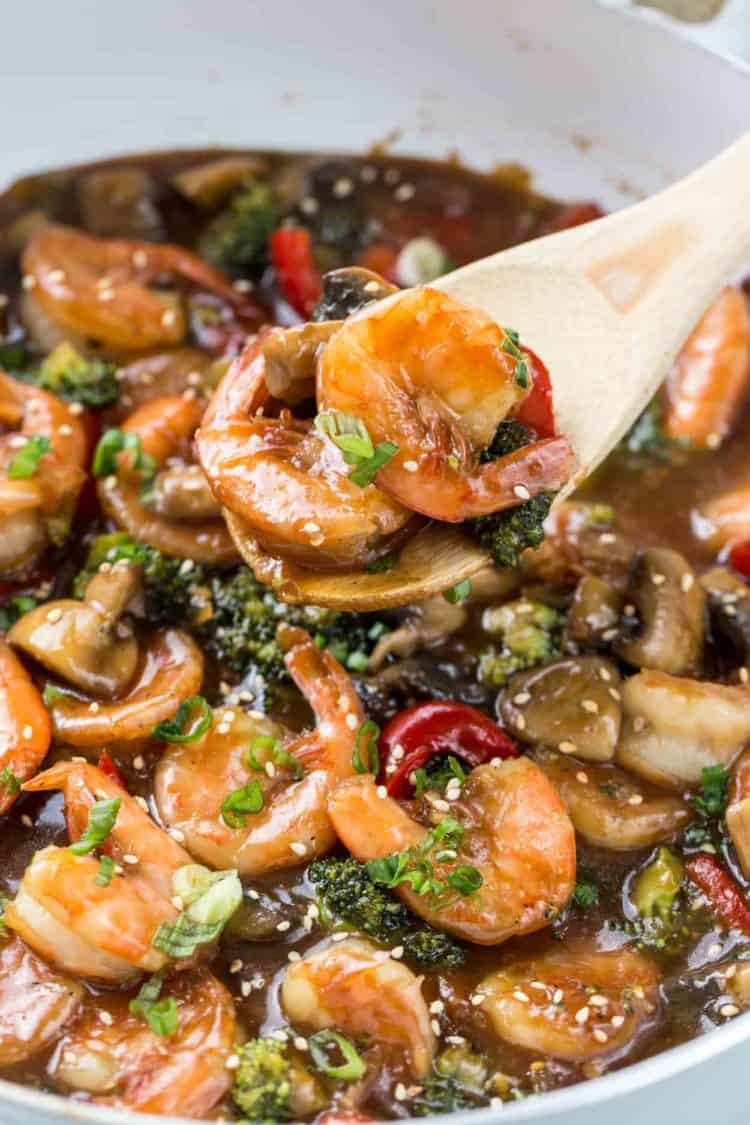 Shrimp recipe in a skillet, with sauteed shrimp on a wooden spatula.
