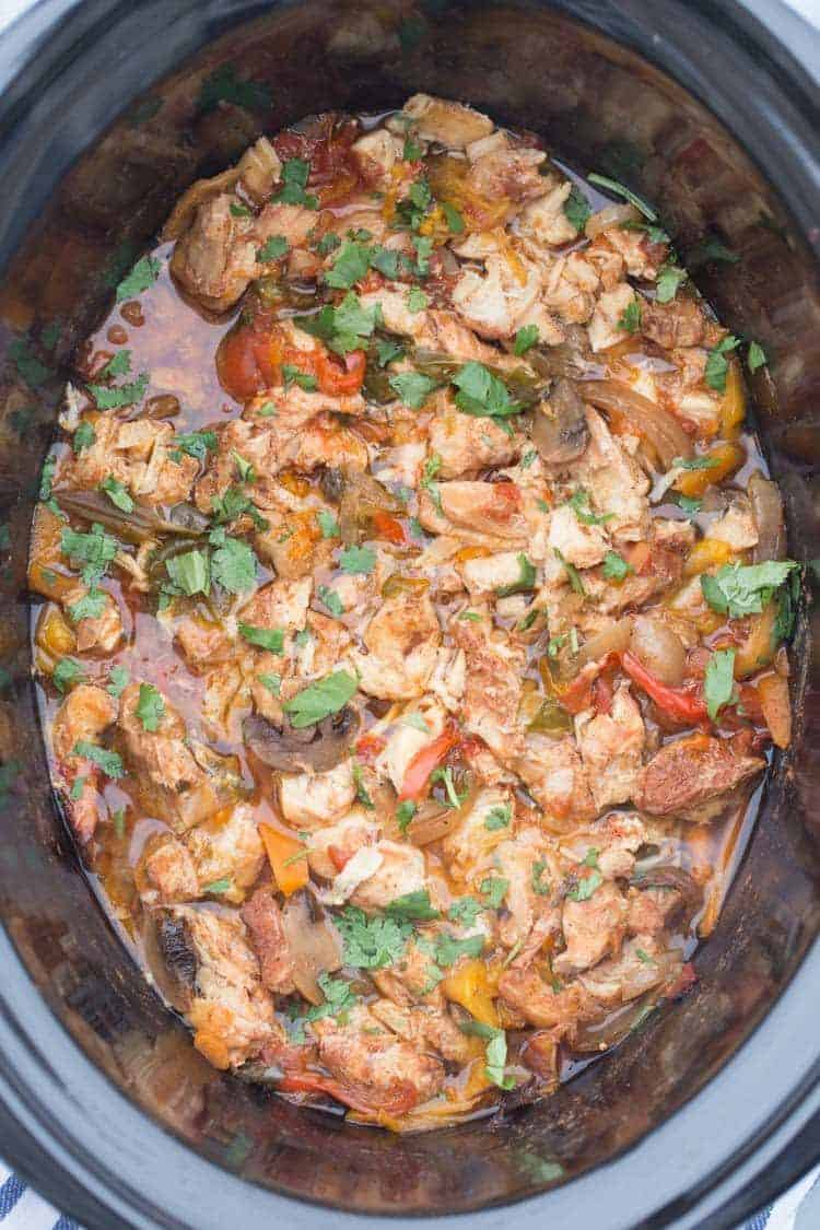 Slow Cooker (Crock-Pot) Chicken Fajita cooked and topped with fresh herbs.
